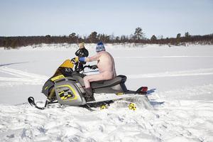 Dresscode för denna kalendergubbe är: mössa, skor, och en Ski-doo. Marit Manfredsdotter fotograferar medan gubben kör runt henne så snön sprutar.