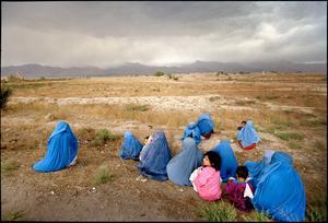 Afghanistan, Norr om Kabul, Shomali dalen.Kvinnor i burka kryper ihop med sina barn medans de väntar på transport till huvudstaden. Daterad till 2002.
