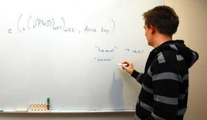 Anders Nylund förklarar hur man genom programmering skyddar ett lösenord på datorn. Han har varit medlem i Mensa i tio år och tycker om samhörigheten i föreningen.