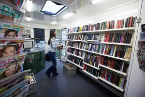 Kerstin Ingegärdsdotter plockar upp återlämnade böcker i hyllorna igen.