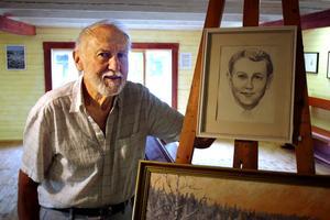 Bengt Forsell bredvid ett blyertsporträtt av sig själv som hans far Nils har tecknat.