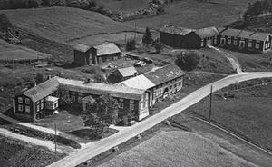 9. Ett flygfoto från 1900-talet visar fastigheten i Östby där Hökarns butik låg. Det är gården längst bort och man kan skymta den väg som gick rakt emot dörren till butiken.Foto: Sockenbilder, Rogsta hembygdsförening