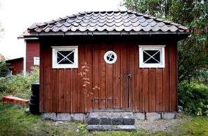 Förrådsbyggnaden på baksidan har valmat tegeltak och små spröjsade fönster.