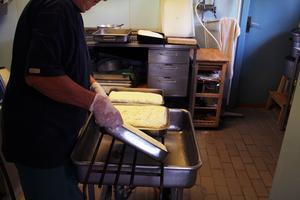 Astrid för över ostmassan i formar och fortsätter hälla av vassla. Men lite vassla blir kvar i formarna, så ostmassan kan koka i vassla under gräddningen i ugnen.