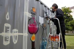 Konstnären och arkitekten Mija Byung arbetar som bäst på att måla containerns fasad inför workshopens introduktion på måndag.