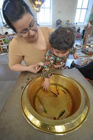 Dop eller dopp. Sara Toma försöker fånga fiskarna i dopfunten, men mamma Zina ser till att det inte blir något dopp.