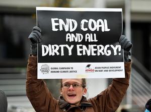 En demonstrant håller upp en skylt om att stoppa kol och smutsig energi utanför lokalen där  klimatmötet COP 23 pågår i Bonn , Tyskland.FOTO: Martin Meissner
