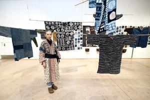 Hisako Hagiwara står framför ett antal av sina klädesplagg.