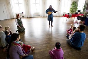 Barnen och deras föräldrar samlas i en halvcirkel på golvet. Tillsammans med Jan Lekare och Liten Karin sjunger de medeltida visor.
