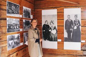 Ulla Westberg visar de gamla fotografierna. Den stora närmast till höger om henne är tagen 1864 av Anders Olsson, Änga.