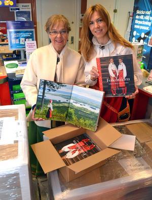 Mejt och Susanne tar fram böckerna från det öppnade paketet.