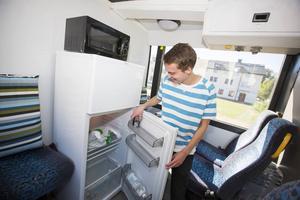 Ett litet kylskåp och ett pentry får plats strax bakom förarplatsen i bussen.