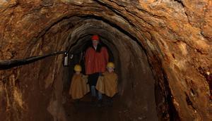 Nora, Åsa och Svea Marnefeldt går försiktigt i gångarna. Efteråt väntar sig mamma Åsa frågor från barnen om livet i gruvan.