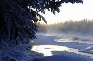 Österdalälven har inte frusit till helt och när morgonsolens första strålar träffar älvens forssande vatten så ryker det om älven när det är minus 34 i luften. Foto:Nisse Schmidt