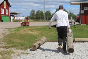 Göthe Hammarström släpar stockar för att göra färdigt en uppiffad parkering inför matchen på lördag.
