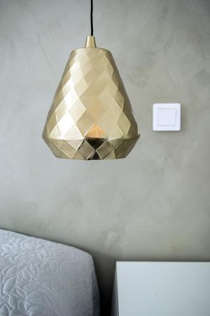 Sänglampan i sovrummet skapar en lyxig effekt mot den målade betongliknande fondväggen.