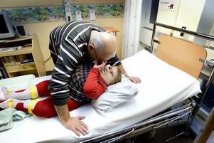Alicia passar på att klappa sin pappa när hon ligger i sjukhussängen och väntar på att få stygnen borttagna.