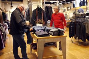 Hans Robertson (till höger), klädhandlare och ordförande för Svensk Handel i Ljusdal och för projektet Ljusdal i centrum, saknar etablering i Ljusdal av någon större affärskedja. Kunden som han samtalar med är Åke Johansson.