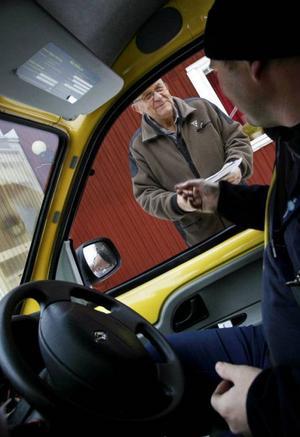 Prat och skoj är det efter vägen när lantbrevbäraren Ola Östlund träffar sina kunder. Här stoppar Gustaf Nilsson i Albacken sina pensionspengar i fickan. Nu blir det Visakortet som gäller. Foto: Henrik Flygare