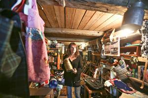 Inger Dahl med sin mammas gamla mjölkruka i loppisen som de har i samma byggnad som vandrarhemmet och studion.