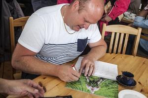 – Rosta varsamt. De kan vara ömma, svarar Pärra Jönsson på frågan om han har något bra recpet på kulpotatis. Här signerar han sin bild i gubbkalendern.