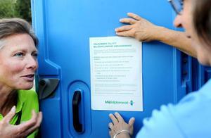 Katarina Wennman och Åsa Törngren tejpar upp miljöinformation på insidan av toadörrarna, där folk har tid att läsa.