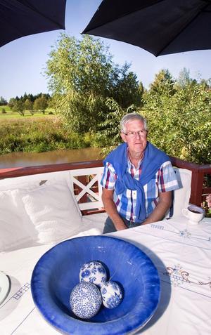 Vitt och blått. Stig Wennsten njuter av att sitta på altanen till kolonistugan vid Svartån, där han också byggt en badbrygga. Foto: Rune Jensen