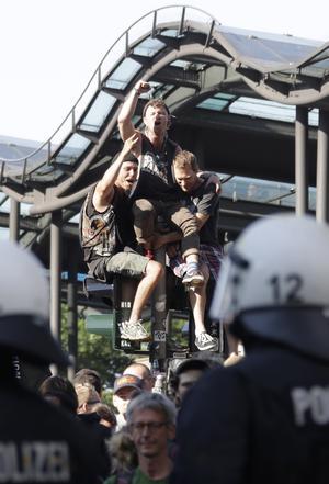 Demonstranter i Hamburg sitter på ett trafikljus när de blockerar en tunnelbanestation.