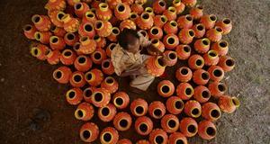 En konstnär målar krukor som ska användas av kvinnor under Navratri.