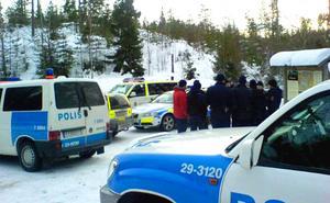 Poliserna överlägger hur de ska lägga upp eftermiddagens arbete på den avspärrade platsen.