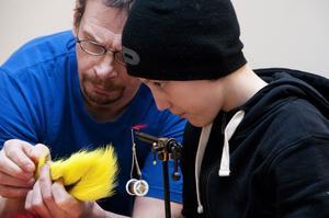 Fastnat på kroken. Rolf Mylläri är i full färd med att visa Casper Stridh hur man binder flugor. Casper går på Atletfiskarnas flugbindningskurs för ungdomar som hålls på söndagar. Foto: Mikael Johansson