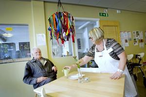 Anna Stangenberg serverar Sören Rydberg en kaffe på träffpunkten för seniorer på Brunnsgatan 59 i Gävle.