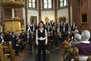 Helena Svartling reciterar texten i Förklädd Gud framför orkestern.