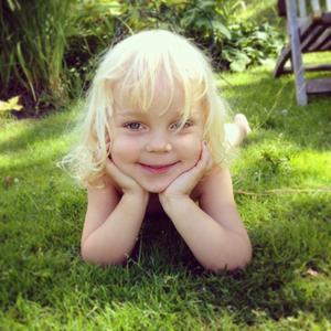 Molly 3 år kopplar av i gröngräset. Foto: Moa Nährström