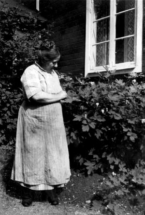 Ellen Brandt utanför hemmet Solglimten, troligen i slutet av 1920-talet. I rabatten har hon löjtnantshjärtan.