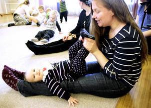 Helena Olofsdotter Borg sitter med dottern Mary-Jill, 13 månader, i knäet och sjunger.