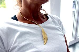 En guldöverdragen fjäder runt halsen.