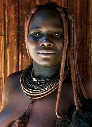 I byn Kamanjab möter vi Uatongota som är insmord med ockra, aska och fett för att göra sig vacker. Huden glänser röd och smälter ihop med den röda jorden. Färgen är inte bara ett skönhetsmedel utan också ett fungerande solskydd.   Foto: Jörgen Ulvsgärd