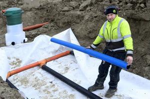 Lasse Persson från Hällbo Entreprenad visar hur en markbädd för rening av spillvatten från en slamavskiljare byggs upp – i en avloppsanläggning som fyller dagens miljökrav.
