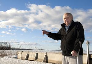 Sigvard Andersson visar utsikten från sommarhuset, där han och hustrun Karin har bott permanent sedan 1987.