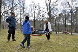 Anki Söderberg och sonen Simon Söderberg får spänna musklerna för att orka bära pappa Peter Söderberg på båren. Scoutledare Thomas Riberg hejar på.