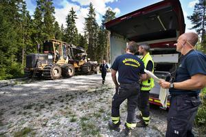 Bilden är tagen första branddagen vid den skogsmaskin, förd av en förare från Ovanåkers kommun, som misstänks ha startat branden och med personal från räddningstjänsten i närheten. När bilden togs hade branden inte utvecklat sig till den största skogsbranden i modern tid.