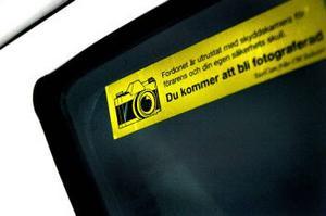 På taxibilarnas rutor finns det gula skyltar som informerar om att kunden kommer att fotograferas när denne går in i bilen.