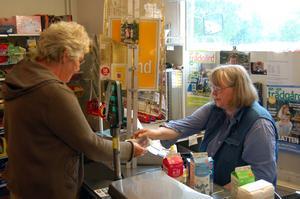 Kassörska. Margareta sitter i lanthandelns kassa och tar emot sina trogna kunder.