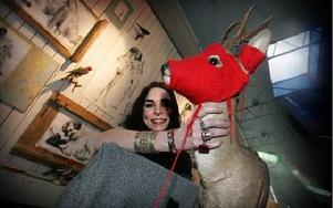 Joanna Ageborn, gästutställare, med ett av sina uppstoppade djur, iklätt röd rånarluva av Rödluvanmodell.