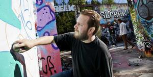 Graffiti-konstnären Daniel Bergstrand vid den lagliga väggen i Norberg.