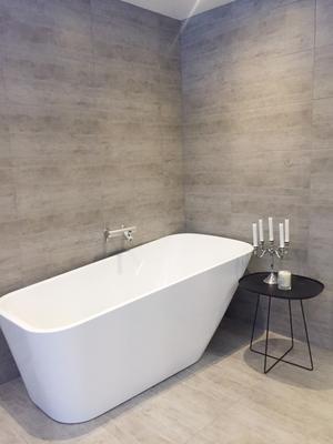 Stilrent badkar. På väggar och golv ett italienskt klinker som familjen har valt genomgående i hela huset –  i badrummet, på gästtoaletten, i hallen, tvättstugan och i köket.