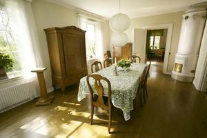 matsal. I huset finns flera kakelugnar. Lampan är två hålmönstrade rislampor som Åsa har satt ihop.