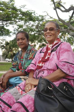Traditionellt klädda Brigitte Iwanejehe och Lucette Bennett njuter av folkvimlet på Place des Cocotiers i centrala Nouméa.