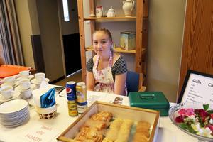 Emilia Norlander säljer fika till besökarna, de nybakade bullarna är populärast då flera vill köpa flera påsar.